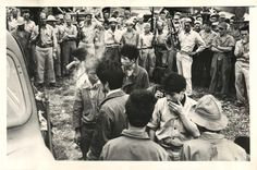 1943- Japanese prisoners, transported to an American base from Guadalcanal, receive American cigarettes and disgusted glances from U.S. troops stationed there.