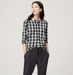 In tomboy-cool gingham, this soft cotton henley is playfully polished. Collarless. Long sleeves with button cuffs. Henley button placket. Shirred beneath forward shoulder seams and back yoke. Shirttail hem.