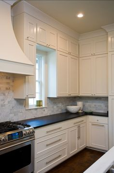 white cabinets, modern handles, black countertops, stainless steel apps & marble backsplash. [design by highland homes, from home bunch]