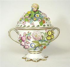 <b>ENGLISH PORCELAIN FLOWER ENCRUSTED VASE AND COVER</b> <br /> 19TH CENTURY <br /> of twin handled urn form with reticulated cover, applied allover with polychrome painted flower decoration and gilt highlights, gilt mark '1580' <br /> 28cm wide, 29cm high