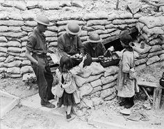 Canadian soldiers buying oranges and chewing gum from French girls somewhere near the front lines, July 1917