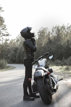 Sexy girl biker and cafe racer motorcycle by JohanJK. Young pretty cheerful woman putting on motorcycle helmet. Girl biker with perfect fit slim body and custom chopper mo.