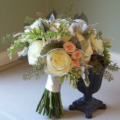 black skeleton leaves, beige stripped coque feathers, Polar Star roses, Princess spray roses, Peach Vision spray roses, scented geranium, seeded eucalyptus, and dusty miller.