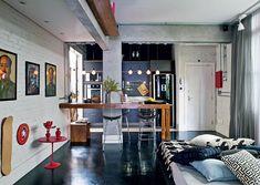 O apartamento de 80 m² ganhou ares de loft com a demolição de várias paredes. Um quarto foi usado para ampliar a sala e a cozinha foi integrada ao living com uma bancada. Assim, o espaço perdeu as delimitações