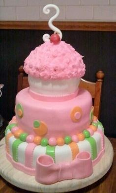 Three tier birthday cake with Giant Cupcake cake on top.