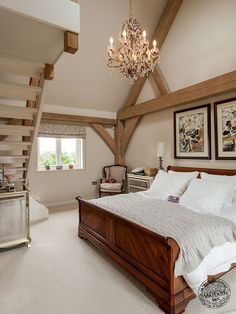 Master Bedroom with Mezzanine Staircase and Exposed Timber Frame by Carpenter Oak Ltd