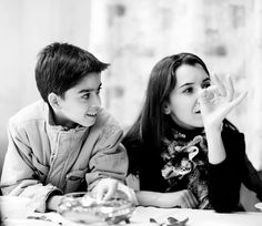 Black and white candid portrait of a mother and son in conversation.