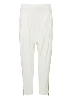 Polyester/Elastane Skinny Harem pant. Comfortable fitting silhouette features a fixed waistband with invisible side zipper, front body tucks and drop crotch with tapered leg complete with exposed gold zippers at hem. Available in various colours as shown.