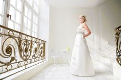 mona berg Kollektion 2015 - Lilie; Modernes Brautkleid aus Satin mit Drapagen, V-Ausschnitt und eleganter Applikation und lässigen Nahttaschen.  Foto: Svea Ingwersen