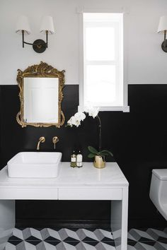 Bathroom with two tone black and white wall, antique gold mirror and vessel sink via Shelby Girard