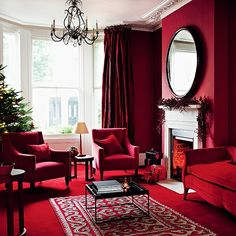 Contemporary Christmas living room with red walls, red carpet, red sofas and berry garland
