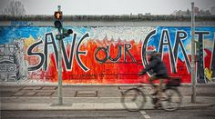 Free photo: person riding bicycle on road near wall with Save Our Earth painting