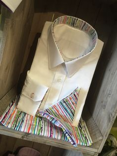 Great British Bespoke White Shirt with contrasting quirky abstract designer Crazy Multy Splash Stripe Inners    Description    The shirt is made up from our beautiful two-fold Poplin. Brightened up by the multi-colored ink splash inner bands on the inside of the collar and cuff, tied together with a contrasting buttonhole on the cuff    The shirt body is a plain white solid poplin.  The quality is a medium weight poplin which uses strong and durable 2 ply yarns.  Solid fabrics are available…