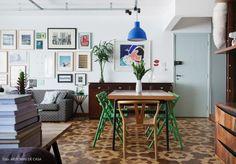 Sala de jantar com mesa de madeira, cadeiras coloridas e buffet vintage.