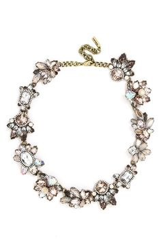 A chain of crystal blossoms in soft shades of champagne and iridescent crystal adds old-world glamour to this vintage-inspired collar necklace.