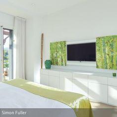Grün ist die Akzentfarbe in dem sonst in weiß gehaltenen Zimmer. Der Fernseher (TV) ist hinter einer Konstruktion aus bedrucktem Holz versteckt.