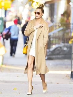 Chrissy Teigen wears a white minidress, camel coat, Chloé bag, pumps, and round sunglasses