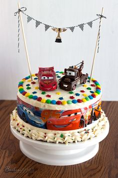 Cars birthday cake! A triple layer cake decorated with white chocolate buttercream, a Cars cake wrap, M&M's, and fun candy sprinkles.