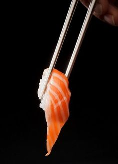 Food Photography: Salmon Roll // Sushi, Salmon, Chopsticks, Front View, Holding, Japanese Cuisine, Asian Food, Artificial Lighting, Black Background, Hand, Utensil Styling, Simple Straightforward Styling
