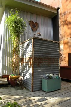 Rusty corrugated metal fits right in for an outdoor shower attached to this artsy home. (eclectic exterior by Sarah Greenman)