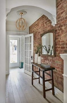 brick flooring A gold sphere pendant accented with a white medallion lights a long foyer hallway boasting a sawhorse console table placed on a gray wash oak floor beneath a reclaimed wooden mirror hung from an exposed brick wall.