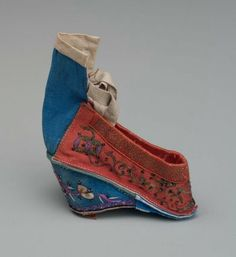 """Woman's shoe (gong xie)      Han Chinese woman's """"lotus foot"""" slipper      Chinese (Han), Qing dynasty, 19th century       China Dimensions     Overall: 10.2 x 7.6 cm (4 x 3 in.) Medium or Technique     Silk satin embroidered with silk and metallic threads, cotton plain weave, leather"""