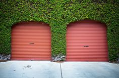 Two red aluminum garage doors on this home are framed in ivy facade for unique, bold look. Red Garage Door, Garage Door Styles, Garage Door Makeover, Garage Door Design, Garage Door Repair, Residential Garage Doors, Garage Door Installation, Cool Garages, Carriage Doors