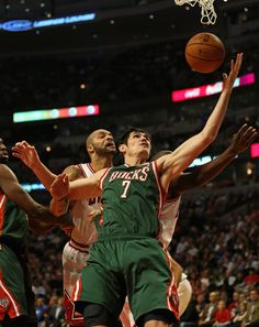 Ersan Ilyasova #7 of the Milwaukee Bucks grabs a rebound under pressure from Carlos Boozer #5 and Loul Deng #9 of the Chicago Bulls at the United Center on November 26, 2012 in Chicago, Illinois.