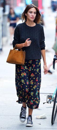 Alexa Chung in a floral maxi skirt, blue cableknit sweater, black Chucks, and a tan purse
