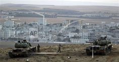 Turkish soldiers hold their positions with their tanks on a hilltop on the outskirts of Suruc, at the Turkey-Syria border, overlooking Kobani, Syria, during fighting between Syrian Kurds and the militants of the Islamic State group, Friday, Oct. 10, 2014. Kobani, also known as Ayn Arab, and its surrounding areas, has been under assault by extremists of the Islamic State group since mid-September and is being defended by Kurdish fighters. (AP Photo/Lefteris Pitarakis)