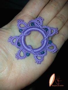 Pendant in tatting, color violet, beads turquoise, on rigid ring.