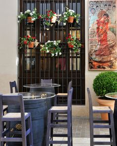 Photograph of a quiet restaurant in Malaga, Spain. Here you can see beautiful art on the wall, painted on ceramic tiles along with flowers