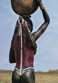 The Dinka woman wearing a corset. Modernity and foreign ideas have permeated Dinka culture and are slowly replacing their traditions and customs. They have adopted either jellabia or European dress and now nudity and wearing of skins are rare sight even in the cattle camps.