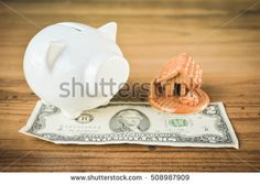 White piggy bank with dollar and little home on wood .selective focus,concept save money for my home