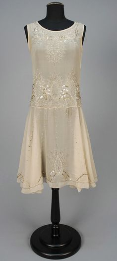 BEADED DANCE DRESS, 1920s. Sleeveless ivory voile decorated with rhinestones, gold sequins and crystal bugle beads, having dropped waist and flared skirt. Front