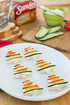 Cucumber Tree Tea Sandwiches: Unexpected holiday guests? Here's a festive appetizer you can whip up in no time! All you need is a tree-shaped cookie cutter, Sara Lee Honey Wheat Bread, chive cream cheese, and thinly sliced cucumber and red pepper.