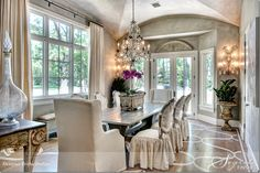Dining room with vaulted ceiling, blended plaster wall treatment, crystal chandelier, large windows, and french doors out to a garden. Designer: Trisha Dodson. Photographer: Wade Blissard