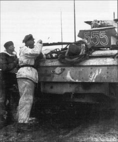 "SS-Hauptsturmführer Hubert Meyer at Kharkov clears a spent shell from his K98. The preceding image has been incorrectly labeled as Kurt Meyer. The facial features clear up this error. Meyer also wore a reversible Panzerkombi.  SS-Hauptsturmführer Hubert Meyer, commander of III./SS-Pz.Gren.Rgt.1 LSSAH.The Panzer IV Turmnummer ""555"" is the the Befehlspanzer of SS-Stubaf. Martin Gross, Abteilungskommandeur of the II.Panzer-Abteilung which supports the III./1 of H.Meyer at Kharkov"