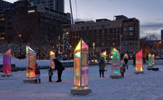 """Prismatica is an astonishing public art installation by Canadian architecture studio RAW. The installation includes 50 prisms made from panels laminated with a dichroic film - this allows the panels to transmit and reflect every color in the visible spectrum.   """"The six and a half-foot-tall structures are spread throughout the Place des Festivals where visitors can walk around all sides of the rotating kaleidoscopes. At night, they display soft-but-colorful lights that illuminate those t..."""