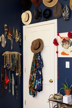 After moving across the country to an urban area, we've had to learn to be very creative with our space and storage. My hats hang along the top of one of our bedroom walls, and the hooks on the back of the door hold my vintage silk robe collection. Most of my necklaces hang here on nails and on this DIY driftwood hanger that I made to custom fit this space.