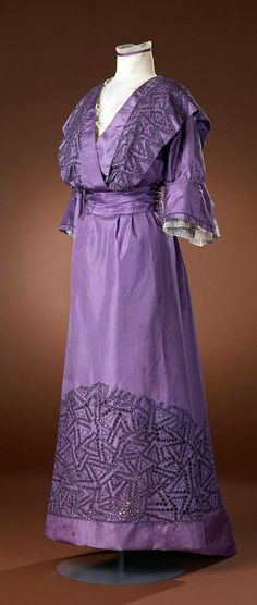 Dress, Hirsch et Cie, ca. 1907-15. Three-piece purple silk gown (bodice, skirt, sash). Openwork fabric patterns on bodice & skirt. Blousing bodice falls into V-neck. Purple silk sash or belt with 2 pendant tassels hanging on closure at back. Amsterdam Museum