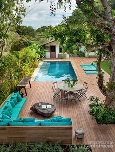 An elegant celebration of turquoise with artful privacy plantings and many kinds of seating.