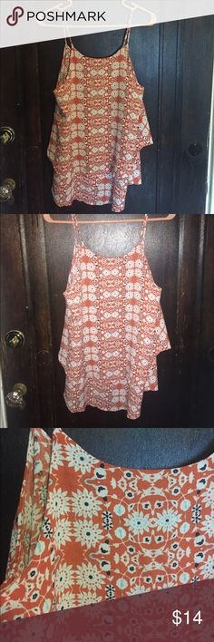 Francesca's Top! Orange thin strapped tank.  Never worn. Two flowy layers at the bottom. Criss cross detail on the back (in pictures). Pretty floral spring and summer pattern! From Francesca's! Francesca's Collections Tops Tank Tops