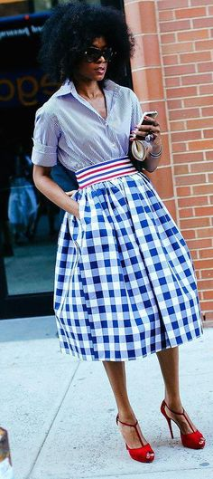 A striped top tucked into a gingham Stella Jean skirt with red heels