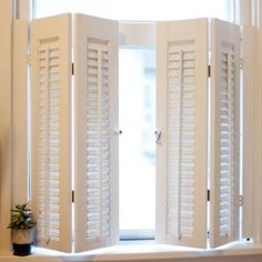 white interior shutters for living and dining room.....I had these in my kitchen in 1983.  I made sure they were larger than the window so even when they were closed they looked like this, zig zaggy....I always loved the zig zaggy look