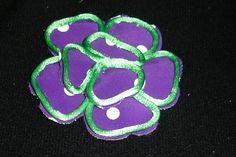 flor confeccionada morada con lunares contorneada con cola de ratón verde.