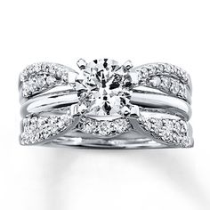 Stunning round diamonds sweep above and below a space for her solitaire engagement ring (sold separately) in this gorgeous enhancer ring. Styled in 14K white gold, the enhancer ring has a total diamond weight of 1/2 carat. Diamond Total Carat Weight may range from .45 - .57 carats.