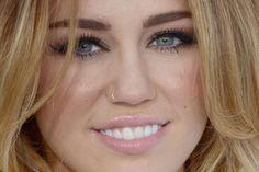 Miley Cyrus deu destaque para os olhos, com cílios postiços, sombra marrom esfumada em toda a pálpebra móvel e delineador gatinho. Ela completa o make com blush bronze nas maçãs do rosto e batom rosinha.