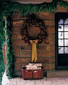 At Skylands, Martha's Seal Harbor, Maine, retreat, the porch is trimmed with a garland and giant wreath, studded with gold and natural pinecones, and tied with a gold ribbon bow. Pink rose hips adorn the garland.