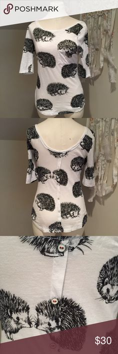 """Hedgehog Top Hedgehog Top - Worn only a few times. In great condition, no flaws, stains, or any other issues that I am aware of at this time. Originally purchased from my local Anthropologie store. 3/4 sleeves, white with black hedgehog print. Has front breast pocket and white buttons with red thread down the back. Back of Shirt has a deep scoop neckline - from the center to bottom of the shirt is 17"""", sleeves are 13"""", from front center neckline to bottom is 21"""". Form fitting in style. 100%…"""